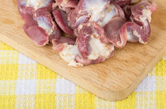 Raw chicken gizzards and hearts on wooden board Stock Photo