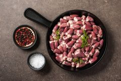 Raw chicken hearts in frying pan, salt and pepper on kitchen tab. Le, top view Royalty Free Stock Photo