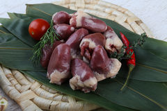 Raw chicken hearts. With pepper and thyme on the bamboo leaves Royalty Free Stock Photo