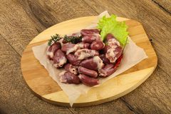 Raw chicken hearts. Heap with thyme branch Royalty Free Stock Image