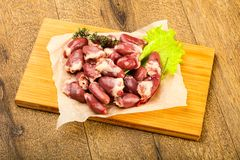 Raw chicken hearts. Heap with thyme branch Stock Photography