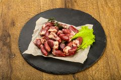 Raw chicken hearts. Heap with thyme branch Stock Photos