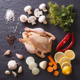 Raw chicken with ingredients for cooking close up on a slate boa Stock Photo
