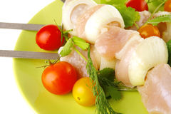 Raw chicken kebabs on dark plate Stock Photography