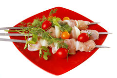 Raw chicken kebabs on red Stock Images