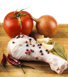 Raw chicken leg on a wooden board with spices and vegetables Stock Photography
