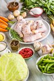 Raw chicken legs with assortment spices and vegetables.  Stock Photography