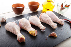 Raw chicken legs on a blackboard. Raw chicken legs lined in a row on the blackboard, there are a number of spices - salt, pepper, olive oil and garlic Royalty Free Stock Photos