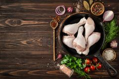 Raw chicken legs on cast iron pan with spices and herbs Royalty Free Stock Photos