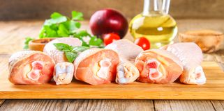 Raw chicken legs on a cutting board on an old wooden table. Raw chicken legs on a cutting board on an old wooden table Stock Photo