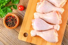 Raw chicken legs on a cutting board on an old wooden table. Raw chicken legs on a cutting board on an old wooden table Royalty Free Stock Photo