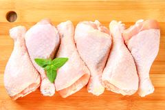 Raw chicken legs on a cutting board on an old wooden table. Raw chicken legs on a cutting board on an old wooden table Royalty Free Stock Photos