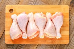Raw chicken legs on a cutting board on an old wooden table. Raw chicken legs on a cutting board on an old wooden table Stock Image