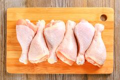 Raw chicken legs on a cutting board on an old wooden table. Raw chicken legs on a cutting board on an old wooden table Stock Photos