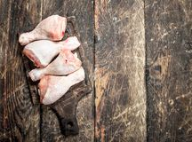 Raw chicken legs on cutting Board. On wooden background Royalty Free Stock Photo