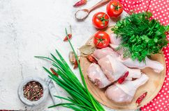 Raw chicken legs on cutting board with spices and herbs. Raw chicken legs on cutting board with fresh parsley and pepper, spices. Food background. Cooking Stock Image