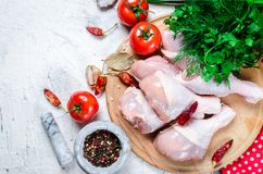 Raw chicken legs on cutting board with spices and herbs. Raw chicken legs on cutting board with fresh parsley and pepper, spices. Food background. Cooking Stock Photography