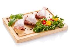 Raw chicken legs on cutting board. Raw chicken legs with vegetables on cutting board Royalty Free Stock Image