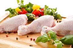 Raw chicken legs on cutting board. Raw chicken legs with vegetables on cutting board Royalty Free Stock Images