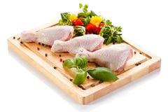 Raw chicken legs on cutting board. Raw chicken legs with vegetables on cutting board Stock Images