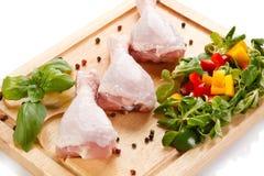 Raw chicken legs on cutting board. Raw chicken legs with vegetables on cutting board Stock Photo