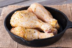 Raw chicken legs in a frying pan on a wooden table. Meat ingredients for cooking. Raw chicken legs in a frying pan on a table. Meat ingredients for cooking Stock Image