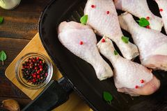 Raw chicken legs in a frying pan on a wooden table. Meat ingredients for cooking. Top view. Raw chicken legs in a frying pan on a wooden table. Meat ingredients Royalty Free Stock Image