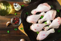 Raw chicken legs in a frying pan on a wooden table. Meat ingredients for cooking. Top view. Raw chicken legs in a frying pan on a wooden table. Meat ingredients Stock Photos