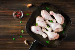 Raw chicken legs in a frying pan on a wooden table. Meat ingredients for cooking. Top view. Raw chicken legs in a frying pan on a wooden table. Meat ingredients Royalty Free Stock Photos