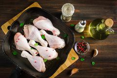 Raw chicken legs in a frying pan on a wooden table. Meat ingredients for cooking. Top view. Raw chicken legs in a frying pan on a wooden table. Meat ingredients Stock Image