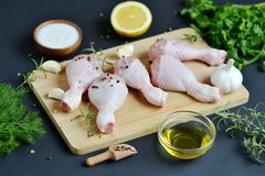 Raw chicken legs with green herbs and spices pepper. On wooden cutting board food ingredient salt rosemary lemon oil preparation lifestyle healthy concept black Stock Photo