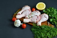Raw chicken legs with green herbs and spices pepper. On wooden cutting board food ingredient salt rosemary lemon oil preparation lifestyle healthy concept black Stock Photography