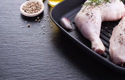 Raw chicken legs with herbs, garlic and tomatoes, ready to cook on a black stone background. Closeup Royalty Free Stock Photo