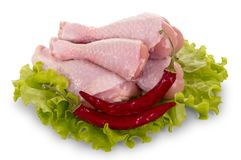 Raw chicken legs, hot pepper and lettuce leaves isolated on whit Royalty Free Stock Images