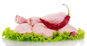 Raw chicken legs, lettuce and red chili peppers isolated on white Royalty Free Stock Images
