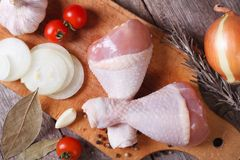 Raw chicken legs and marinade ingredients on a kitchen board Stock Image