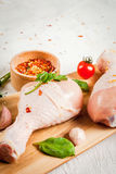 Raw chicken legs. Meat, a source of protein. On a cutting board, on a white stone table. With spices, herbs and tomatoes for cooking. Copy space Stock Image