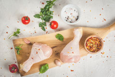 Raw chicken legs. Meat, a source of protein. On a cutting board, on a white stone table. With spices, herbs and tomatoes for cooking. Top view copy space Royalty Free Stock Photography
