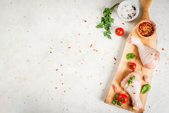 Raw chicken legs. Meat, a source of protein. On a cutting board, on a white stone table. With spices, herbs and tomatoes for cooking. Top view copy space Stock Photos