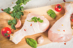 Raw chicken legs. Meat, a source of protein. On a cutting board, on a white stone table. With spices, herbs and tomatoes for cooking. Top view copy space Stock Image