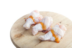 Raw chicken legs with oyster sauce on white background. Raw chicken legs on wooden cutting boards on white background Royalty Free Stock Images