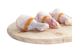 Raw chicken legs with oyster sauce on white background. Raw chicken legs on wooden cutting boards on white background Royalty Free Stock Photo