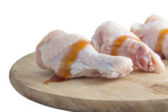 Raw chicken legs with oyster sauce on white background. Raw chicken legs with oyster sauce on wooden cutting boards on white background Royalty Free Stock Photography