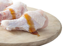 Raw chicken legs with oyster sauce on white background. Raw chicken legs with oyster sauce on wooden cutting boards on white background Royalty Free Stock Photos