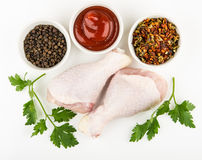 Raw chicken legs, parsley and bowls with spices and ketchup Stock Photography