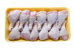 Raw chicken legs in plastic tray on white background. Raw chicken legs in yellow plastic tray isolated on white background stock photography