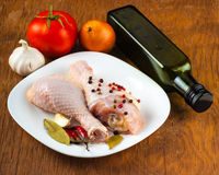 Raw chicken legs on the plate with spices. Wood background Royalty Free Stock Images