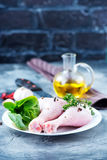 Raw chicken legs. On plate and on a table Royalty Free Stock Images