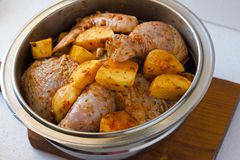 Raw chicken legs with raw potatoes with spices for baking on a wooden table. Meat ingredients for cooking.  Stock Photos