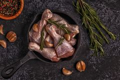 Raw chicken legs with rosemary, garlic and chilli. Stock Images